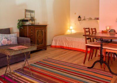 Ansicht der Wohnung mit Tisch, Bett und Sofa